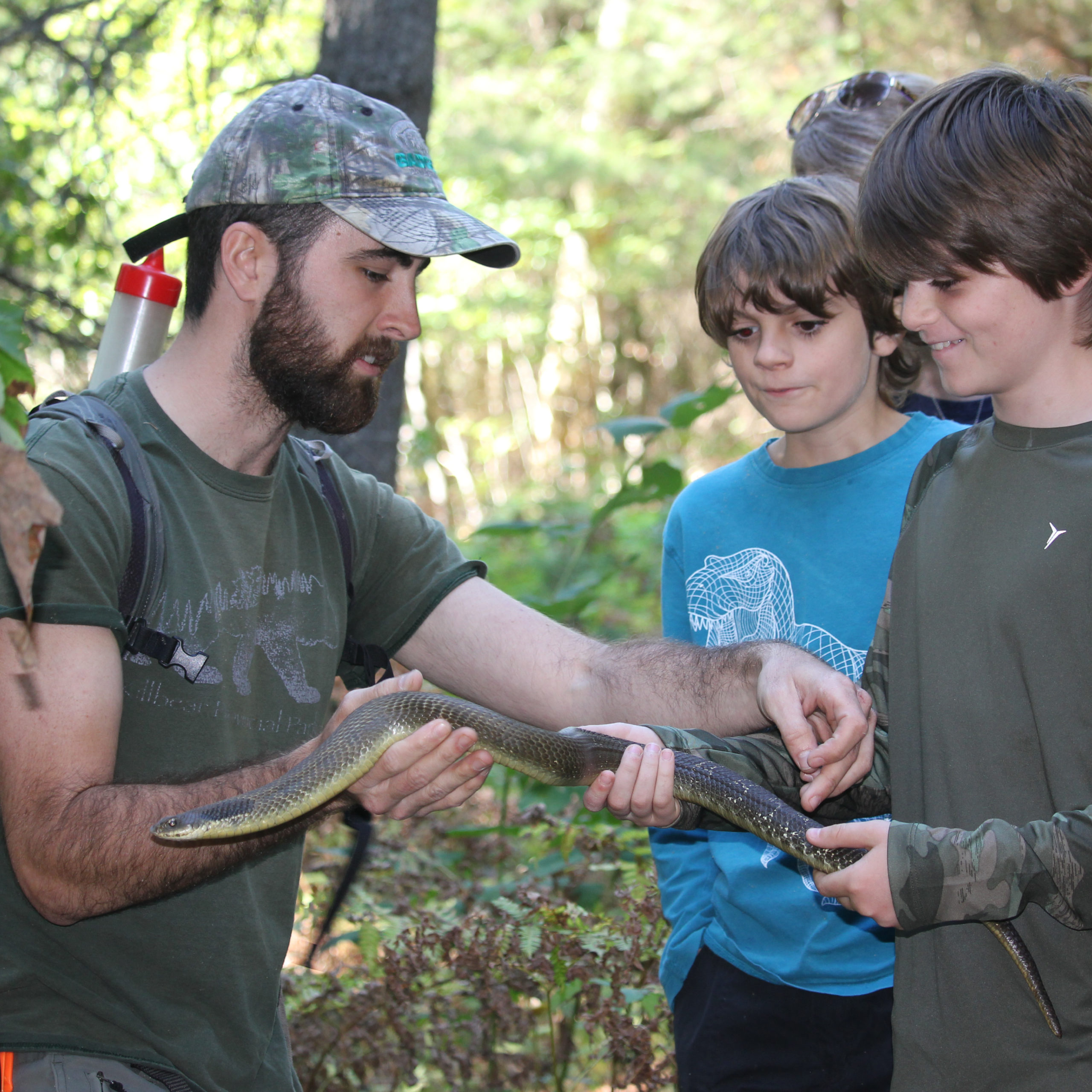 Rattlesnake lead biologist Eric Jolin with an eastern hog-nosed snake in northern Ontario with some help from the next generation of young conservationists.